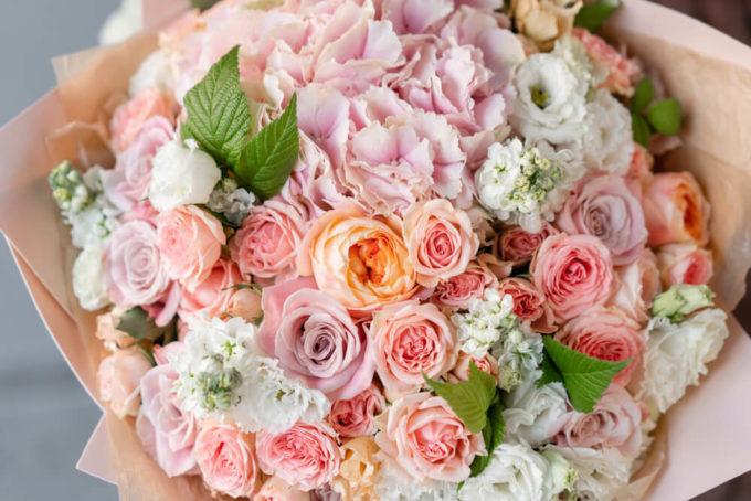 ありがとうの感謝や尊敬の花言葉をもつバラの花束をプレゼントする様子