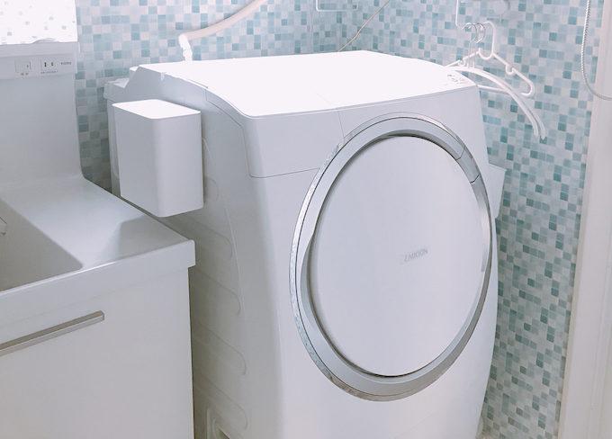 洗面所の浮かせる収納。洗濯機の横に洗剤を浮かせて収納する様子